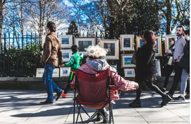 Local artist keeping an eye on her work for sale at the Sunday art market on Merrion Square